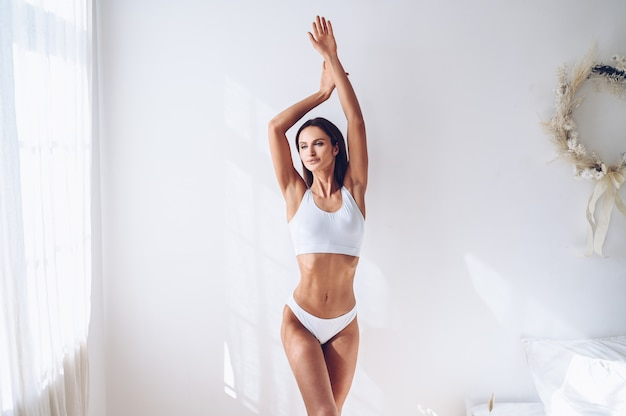 Young fit woman in white lingerie on white wall isolated. muscular slim attractive female with flat belly. copy space for text. body care, healthy and sporty life, hair removal, yoga concept