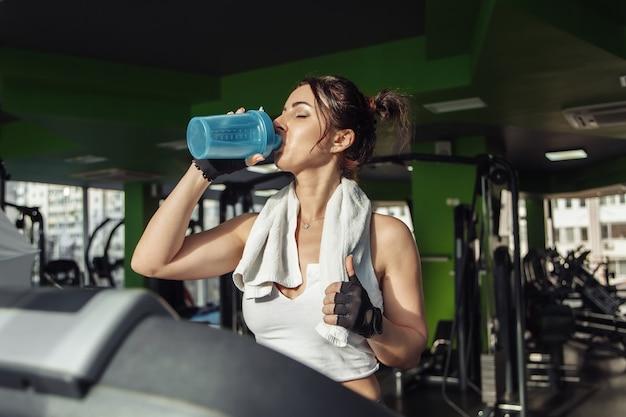 肩にタオルを持った若いフィットの女性は、トレッドミルで水を飲みます。減量の概念、有酸素運動