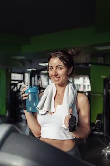 トレッドミルで水のボトルを保持している彼女の肩にタオルを持った若いフィットの女性。減量の概念、有酸素運動
