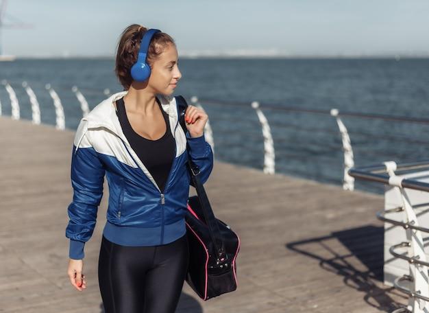 훈련 가방과 밝고 화창한 날에 해변 산책로를 따라 걷는 헤드폰 젊은 맞는 여자