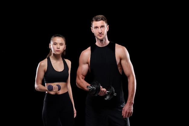 Молодая подтянутая женщина с гантелями и мускулистый спортсмен со штангой тренируются вместе