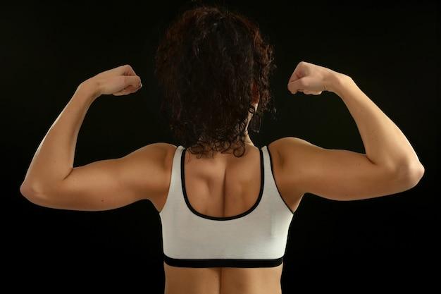 黒の背景、背面図にダンベルを持つ若いフィット女性