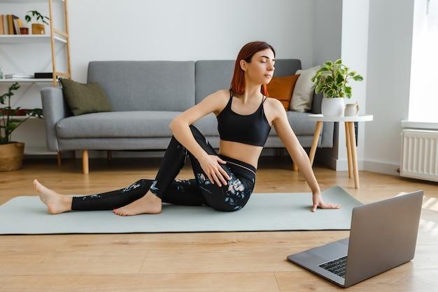 Молодая здоровая женщина с ноутбуком смотрит онлайн-видеоуроки и занимается йогой дома