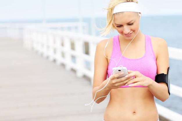 Молодая женщина подходит с телефоном на пирсе