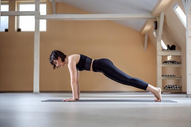 Young fit yogi woman in plank yoga pose. yoga studio interior.