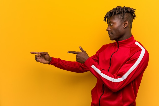Young fitness african man excited pointing with forefingers away.