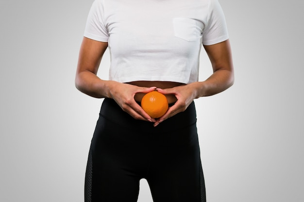 Young fitness afro woman holding an orange