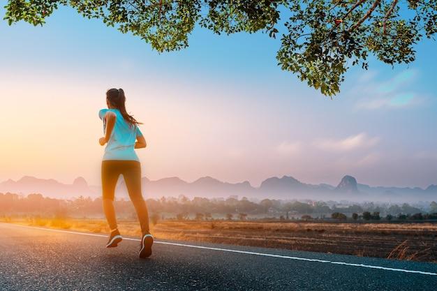 젊은 피트니스 아시아 여자는 라이프 스타일 건강을 위해 아침에 도로에서 야외 운동을 실행하고 조깅합니다.
