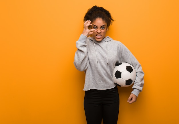 Young fitness black woman angry and upset. holding a soccer ball.