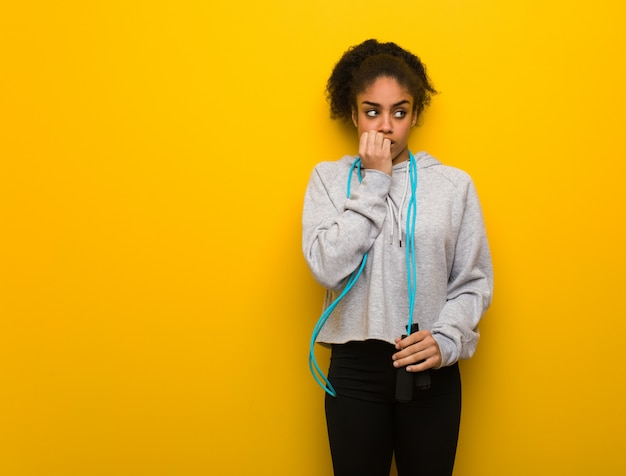 Young fitness black woman biting nails, nervous and very anxious. holding a jump rope.