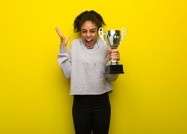 若いフィットネス黒人女性の勝利を祝う