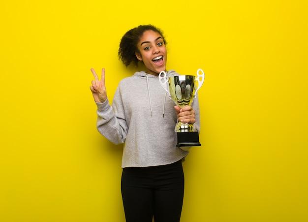 勝利のジェスチャーをしている若いフィットネス黒人女性