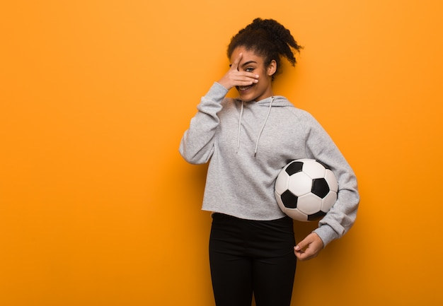 Young fitness black woman embarrassed and laughing at the same time. holding a soccer ball.