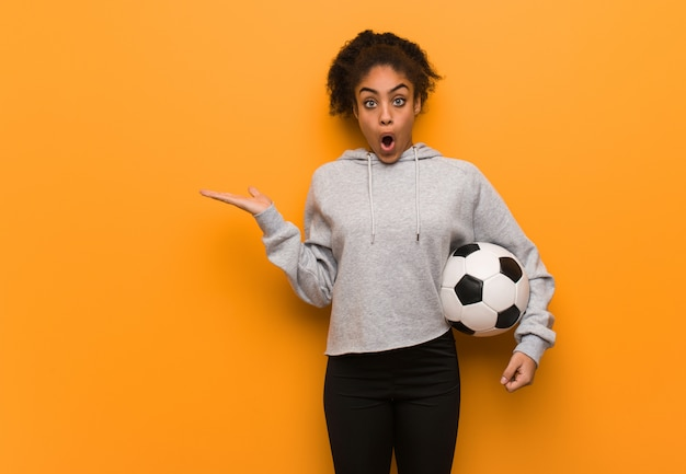 Young fitness black woman holding something on palm hand. holding a soccer ball.