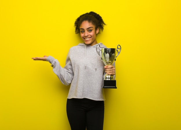 Young fitness black woman holding something with hand