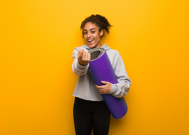Young fitness black woman inviting to come. holding a mat.