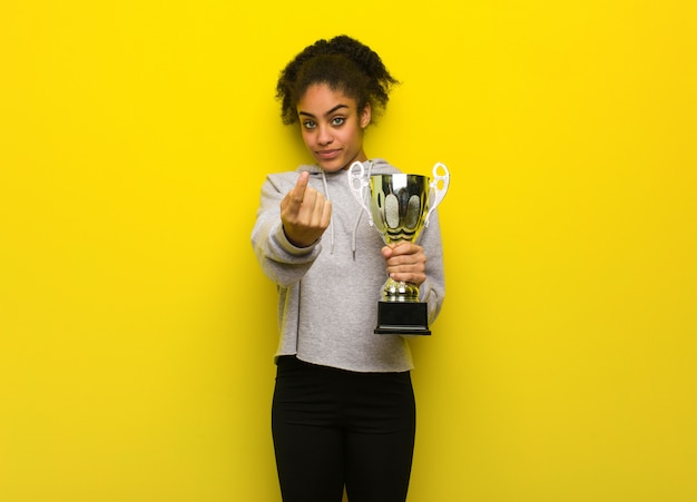 Young fitness black woman inviting to come. holding a trophy.