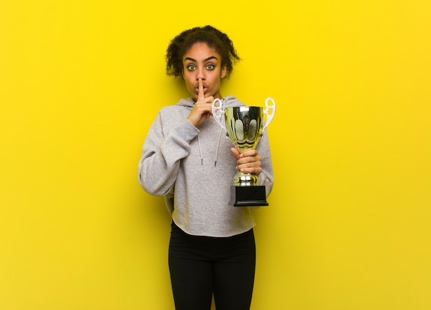 Young fitness black woman keeping a secret or asking for silence. holding a trophy.