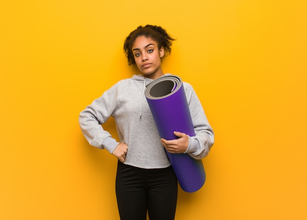 Young fitness black woman looking straight ahead. holding a mat.