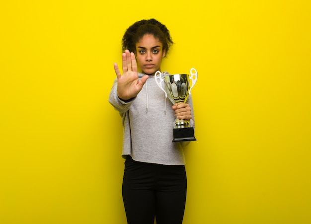 Young fitness black woman putting hand in front. holding a trophy.