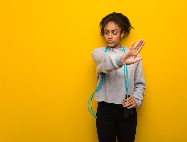 Молодая чернокожая женщина фитнеса кладя руку вперед. держит скакалку.