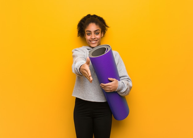 Young fitness black woman reaching out to greet someone. holding a mat.