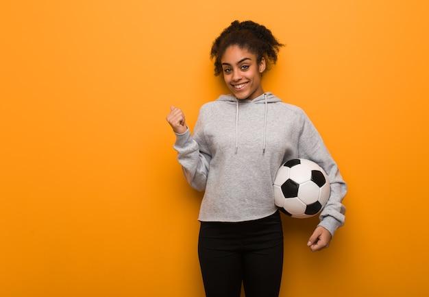 Молодая чернокожая женщина фитнеса улыбается и указывает в сторону. держит футбольный мяч.