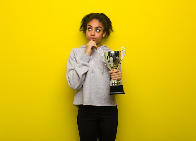 Young fitness black woman thinking about an idea. holding a trophy.
