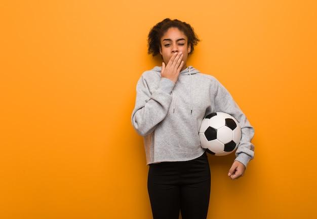 젊은 피트니스 흑인 여성 피곤하고 매우 졸려. 축구 공을 들고.