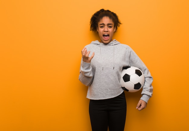 Young fitness black woman very scared and afraid. holding a soccer ball.