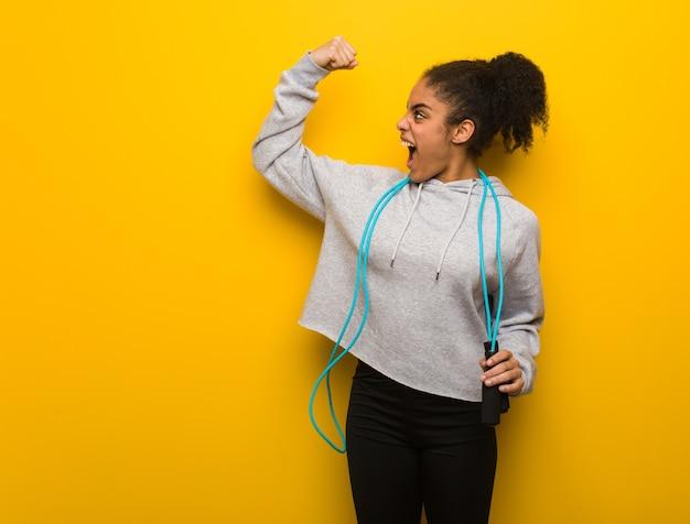 Молодая черная женщина фитнеса, которая не сдается. держит скакалку.