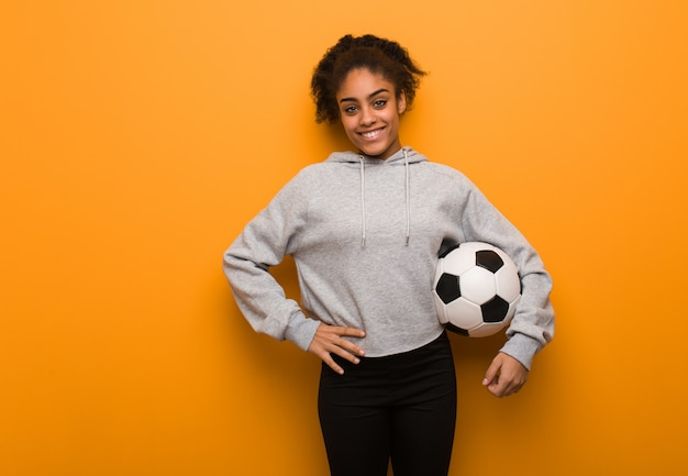 Young fitness black woman with hands on hips. holding a soccer ball.