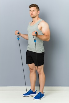 Young fitness caucasian man practicing with an elastic band.