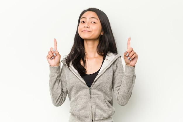 若いフィットネス中国人女性は、両方の前指で空白を示しています。