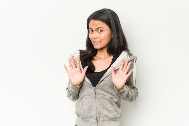 Young fitness chinese woman rejecting someone showing a gesture of disgust.