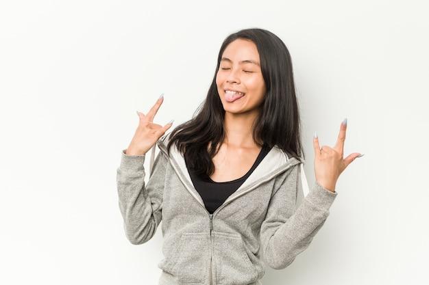 指で岩のジェスチャーを示す若いフィットネス中国の女性
