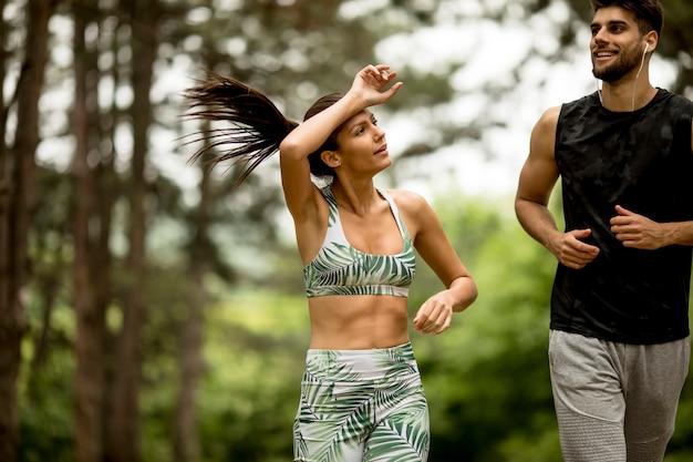 森林歩道で実行されている若いフィットネスカップル