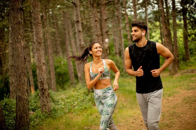 Young fitness couple running at the forest trail on a summer day
