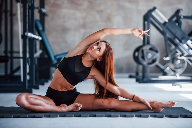 Young fitness girl in black sportive clothes doing yoga exercises in gym.