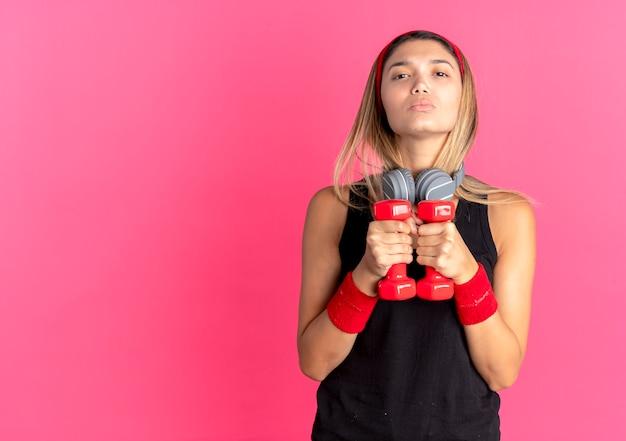 Giovane ragazza di forma fisica in abiti sportivi neri e fascia rossa facendo esercizi con manubri guardando fiduciosi sul rosa