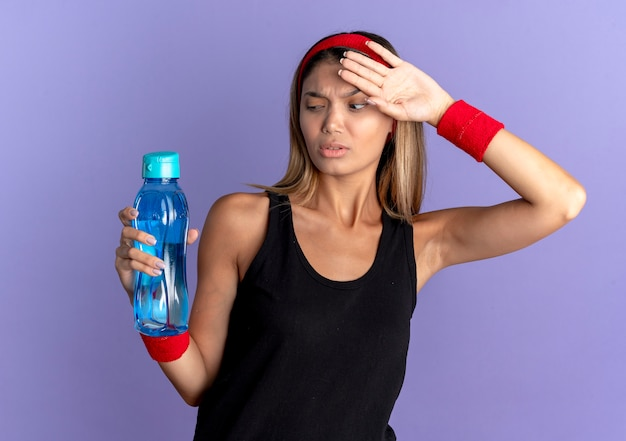 Giovane ragazza di forma fisica in abiti sportivi neri e fascia rossa che tiene una bottiglia d'acqua cercando stanco ed esausto dopo l'allenamento in piedi sopra la parete blu