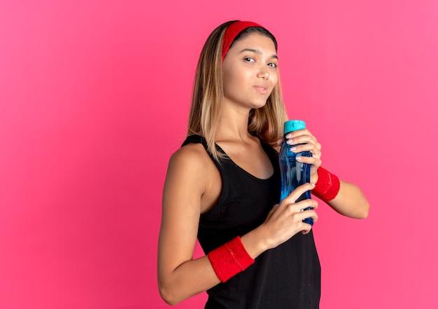 Giovane ragazza di forma fisica in abiti sportivi neri e fascia rossa che tiene una bottiglia d'acqua sorridente fiducioso sul rosa