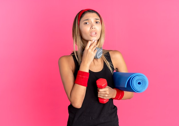 Young fitness girl in black sportswear and red headband holding dumbbell and yoga mat confused over pink