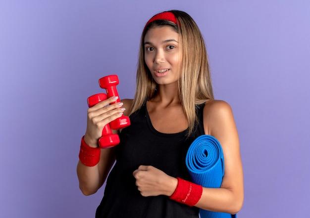 Giovane ragazza di forma fisica in abiti sportivi neri e fascia rossa che tiene i manubri e stuoia di yoga che guarda l'obbiettivo sorridente fiducioso in piedi sopra la parete blu