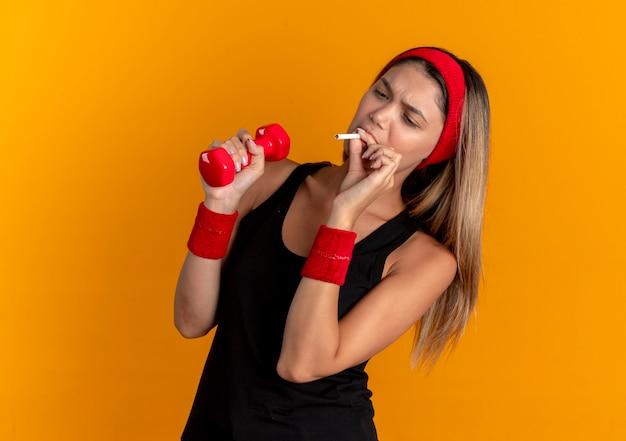Giovane ragazza di forma fisica in abiti sportivi neri e fascia rossa che tiene il manubrio e fumare un concetto di cattiva abitudine di sigaretta in piedi sopra la parete arancione
