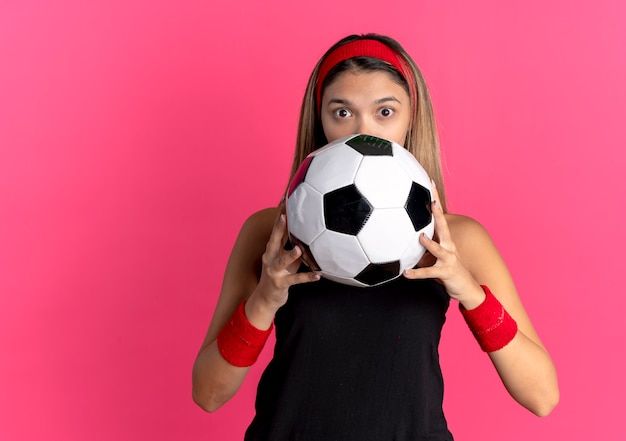 Giovane ragazza di forma fisica in abiti sportivi neri e fascia rossa che tiene il pallone da calcio che sembra sorpreso nascondendo il suo viso in piedi sopra la parete rosa