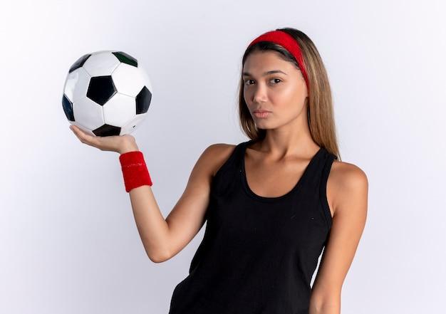 Giovane ragazza di forma fisica in abiti sportivi neri e fascia rossa che tiene pallone da calcio con la faccia seria che sta sopra il muro bianco