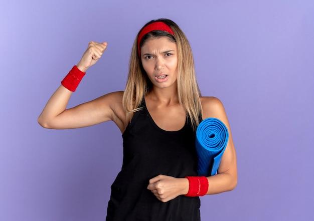 Giovane ragazza di forma fisica in abiti sportivi neri e fascia rossa che tiene la stuoia di yoga che alza il pugno con la faccia arrabbiata che sta sopra la parete blu