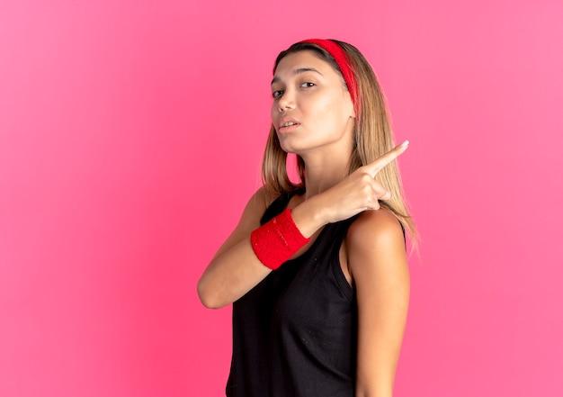 Giovane ragazza di forma fisica in abbigliamento sportivo nero e fascia rossa che sembra sicura che punta indietro sopra il rosa