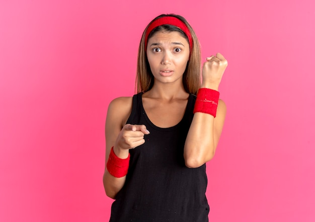 Young fitness girl in black sportswear and red headband looking confused clenching fist pointing with finger at camera over pink
